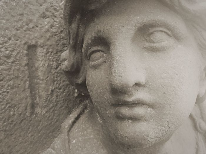 Close-up portrait of female statue against wall