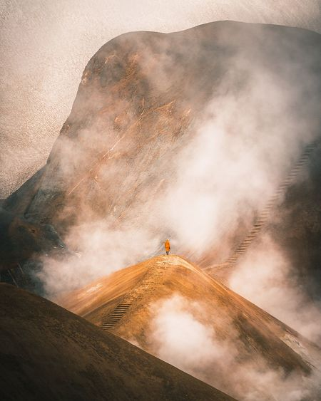 Person standing on mountain against sky