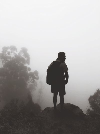 Rear view of silhouette young man with backpack standing on mountain during foggy weather