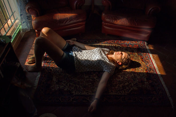 High Angle View Of Mature Woman Sleeping On Carpet A Home