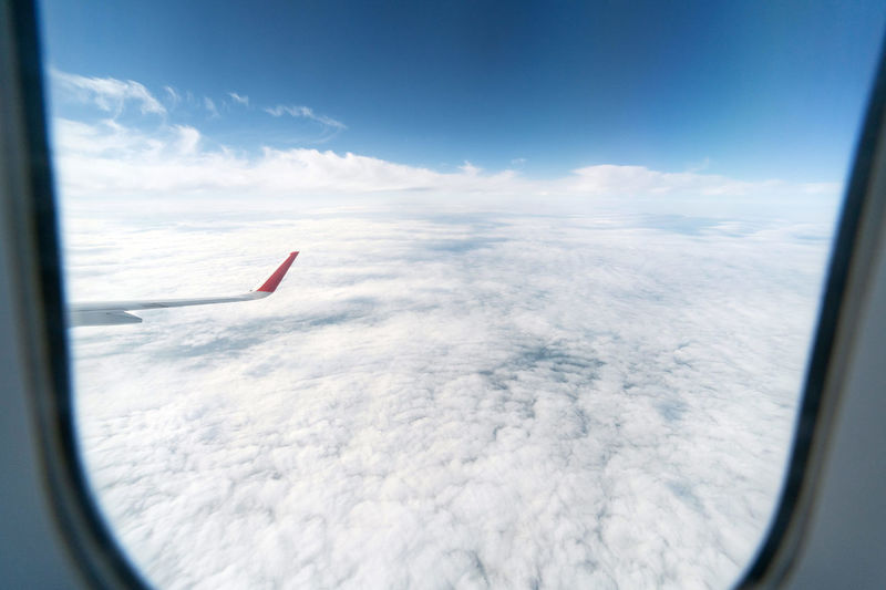 Airplane flying over glass window against sky
