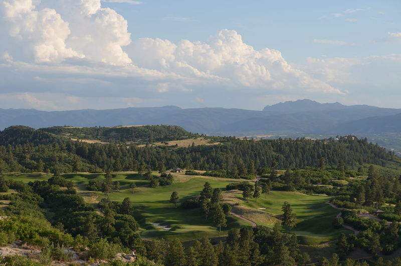 High Angle View Of Golf Course And Mountains Against Sky
