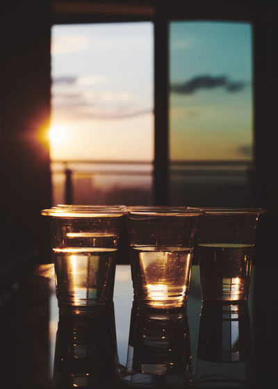 Close-up of beer glass on table against sunset sky