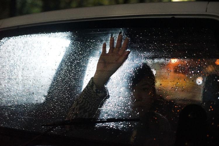 Woman seen through wet glass window