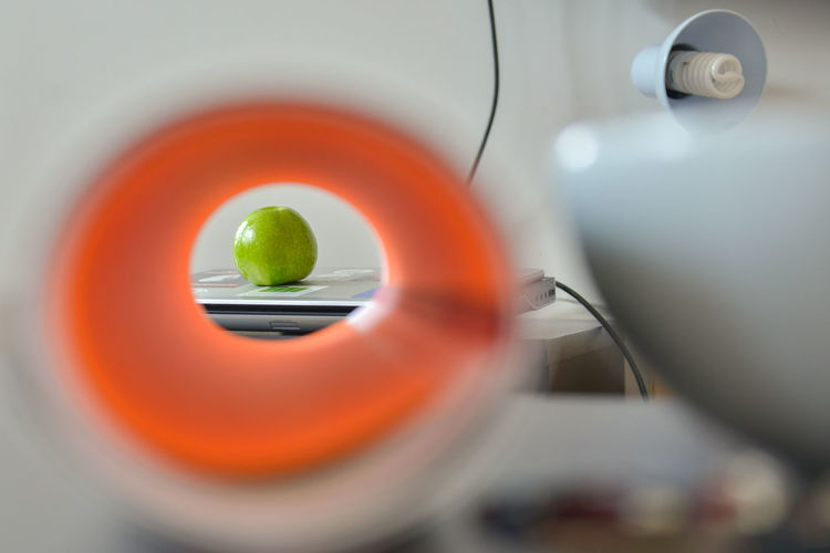 Apple through the paper roll Accuracy Appliance Close-up Electrical Equipment Focus On Background Food Food And Drink Fruit Geometric Shape Green Color Healthcare And Medicine Healthy Eating Indoors  No People Orange Color Science Selective Focus Still Life Table Technology Wellbeing