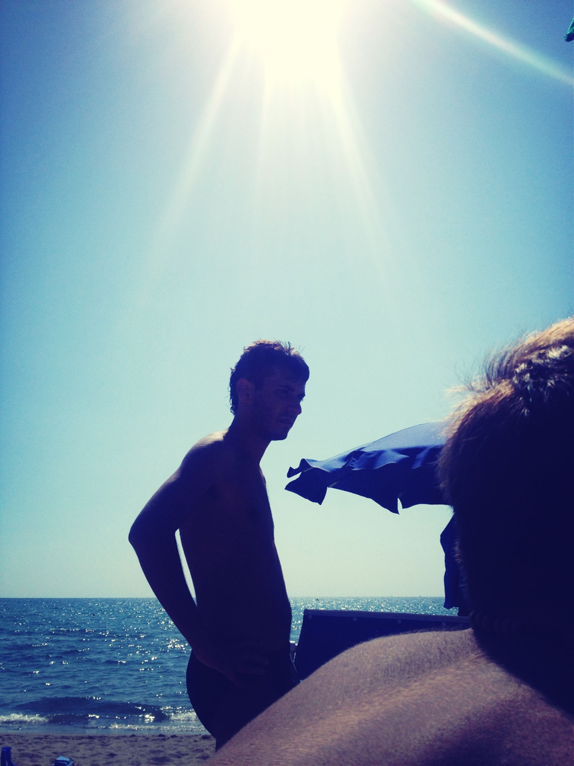 sea, lifestyles, water, leisure activity, sunlight, horizon over water, rear view, men, sunbeam, sun, clear sky, sky, blue, beach, person, holding, vacations, lens flare