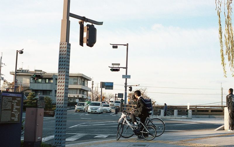 Man riding bicycle on street in city against sky