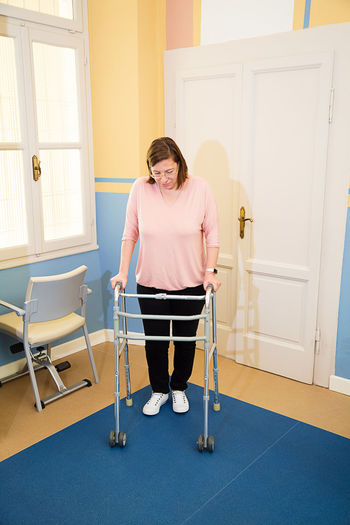 Full length of woman with mobility walker at home