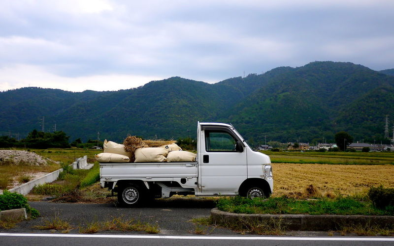 Agriculture Cloud - Sky Field Land Vehicle Loaded Truck Mountain Range No People Non-urban Scene Parked Rice Field Rural Scene Sacks Of Rice Small Truck Stationary Tranquil Scene Transportation Truck
