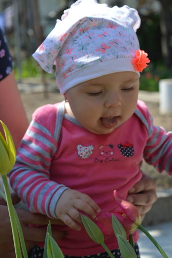 Close-up of cute baby girl sticking out tongue outdoors