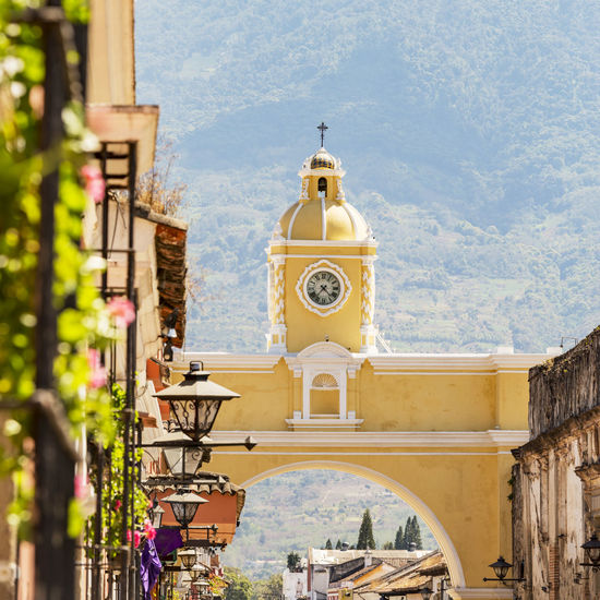 Antigua Guatemala, classic colonial town with famous Arco de Santa Catalina and Volcan de Agua behind Built Structure Building Exterior Architecture Religion Building Belief Spirituality Place Of Worship Day Nature Bell Tower - Tower Tower Travel Destinations The Past Outdoors Plant History No People Clock Antigua Guatemala Guatemala