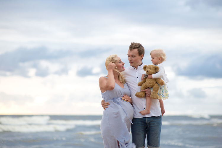 Arm Around Baby Bonding Carrying Childhood Day Embracing Family Family With One Child Father Happiness Holding Love Men Mother Nature Sea Sky Smiling Son Standing Teddy Bear Togetherness Water Women