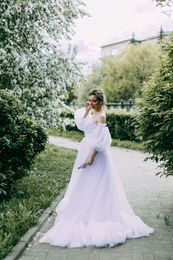 A beautiful delicate woman bride in a wedding dress walks alone in a blooming spring outdoor park
