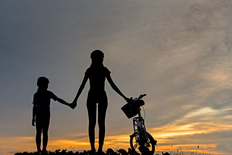 Silhouette people with bicycle against sky during sunset