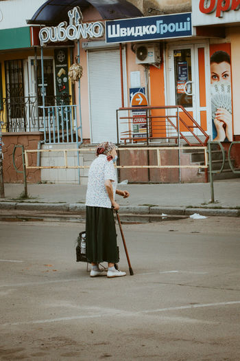 Woman standing on street against building in city