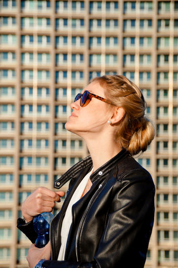 Side View Of Young Woman In Sunglasses Standing By Building In City