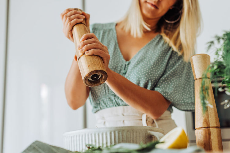Midsection of woman holding ice cream at home