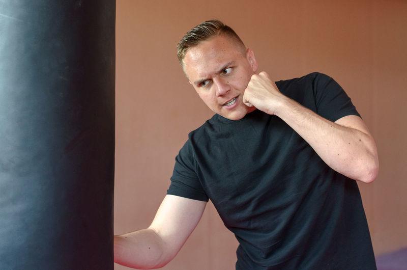 Angry man hitting punching bag against wall