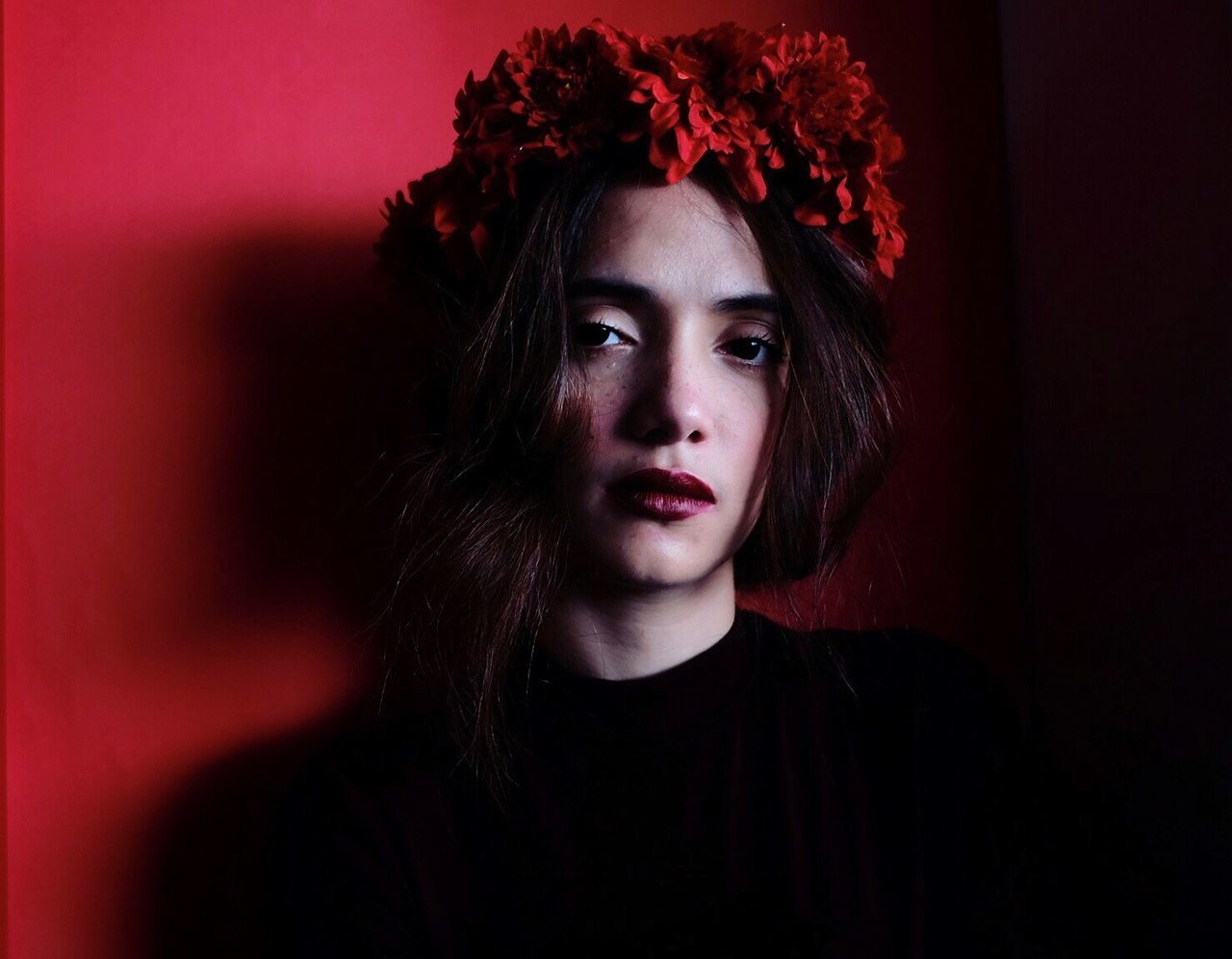 PORTRAIT OF YOUNG WOMAN WITH RED FLOWER AT HOME