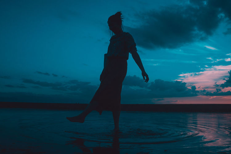 Silhouette man standing in sea against sky during sunset