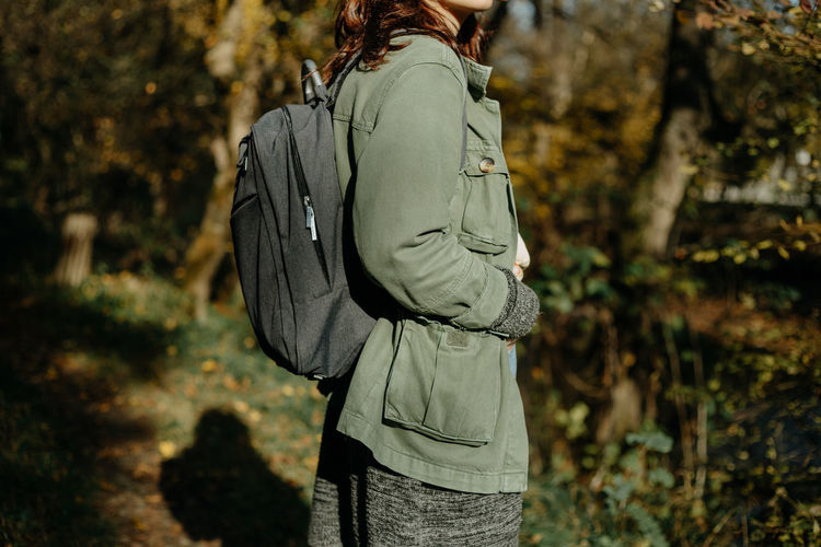 Rear view of woman standing against trees in forest