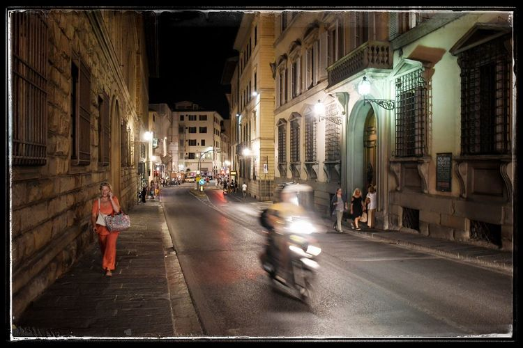 People on road amidst buildings in city at night