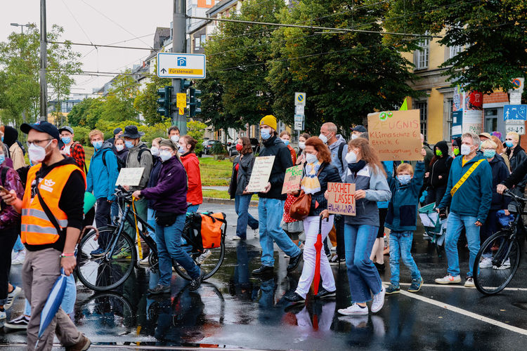 Group of people on road against trees in city