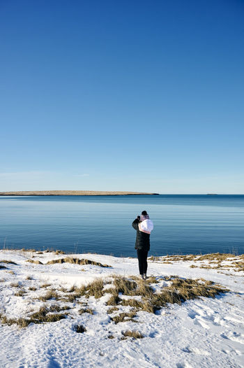 Rear view of man standing on shore against clear sky