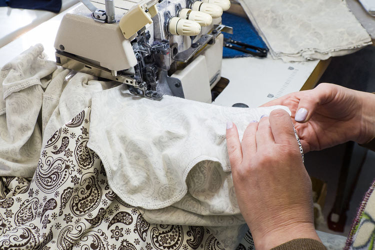 Cropped hand of woman sewing at factory