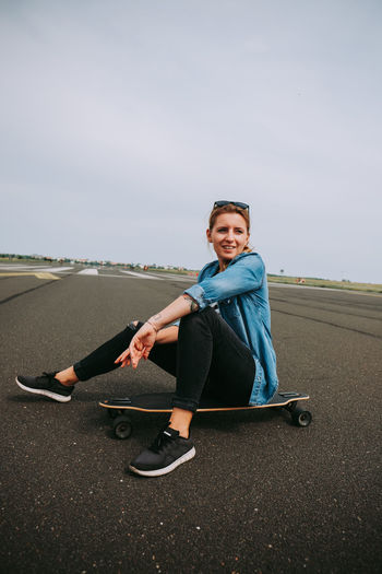 Portrait of man sitting on skateboard