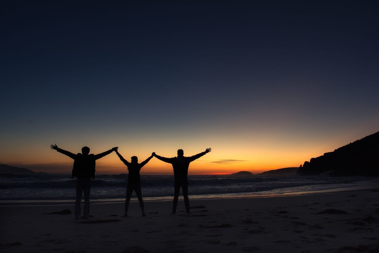 Silhouette people standing at beach against clear sky during sunset
