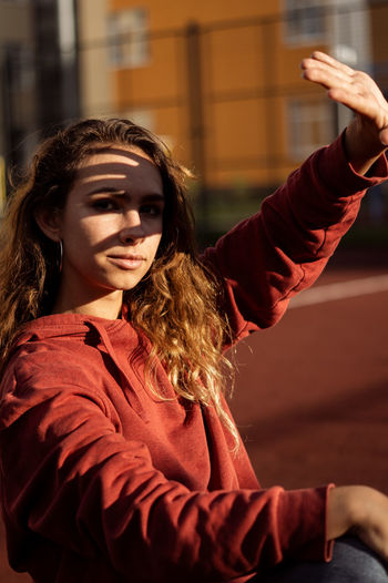 Portrait of young woman shielding eyes while sitting in sports court