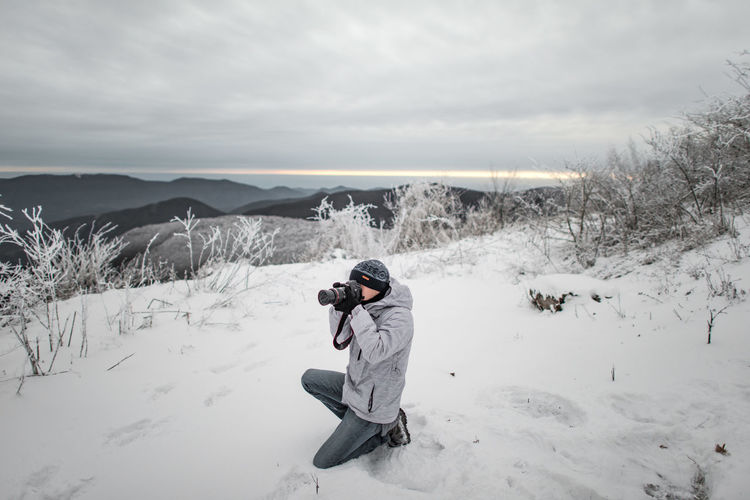 Man photographing while kneeling on snow covered landscape