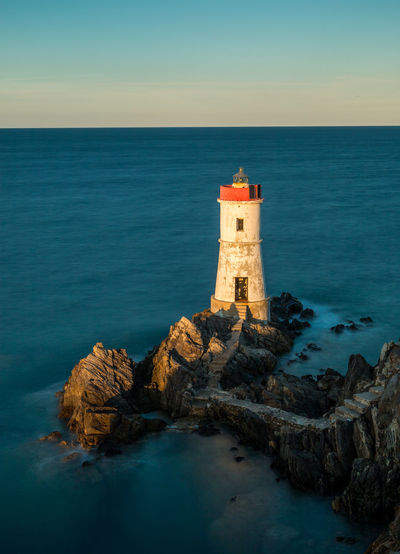 Lighthouse on rock by sea against sky