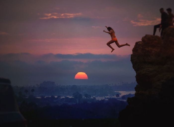 Women jumping from rock against cloudy sky