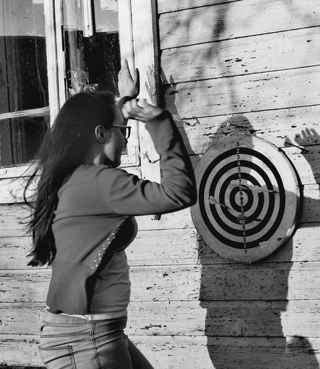 Side View Of Young Woman Aiming On Dartboard Against Wooden Wall