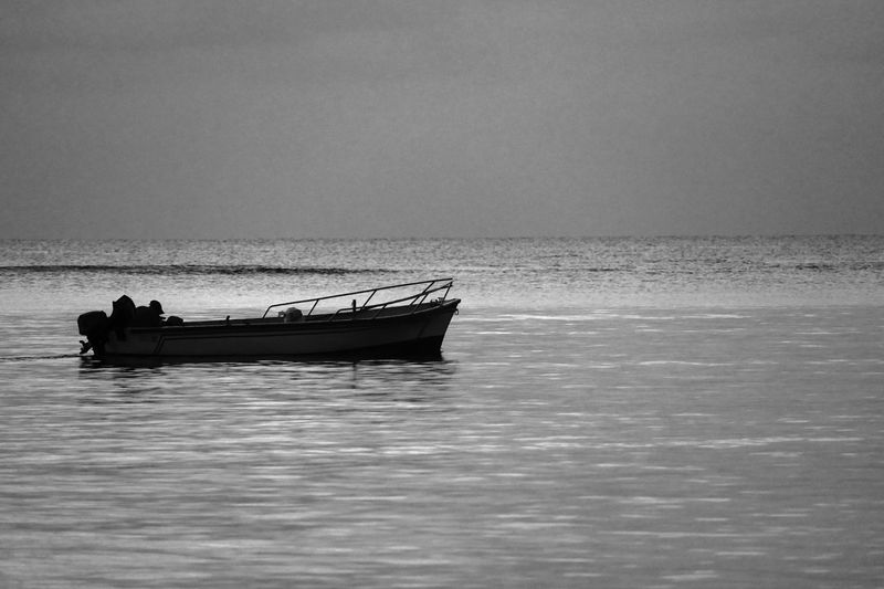 Black And White Image Of Fishing Boat Against Ocean Reflection Sea Water Nature Sky Black And White Travel Loneliness Black & White Tranquility Transportation Horizon Nature Photography Mauritius B & W  Beauty In Nature Horizontal Copy Space Tranquil Scene Nautical Vessel Horizon Over Water Mode Of Transportation Waterfront Real People Clear Sky Outdoors Day Scenics - Nature