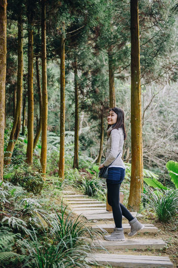 Side View Of Smiling Woman In Forest