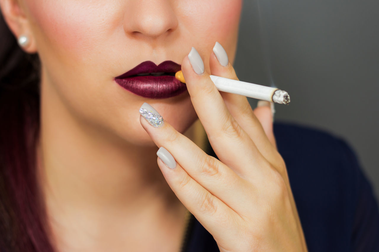 Midsection Of Young Woman Smoking Cigarette Against Gray Background