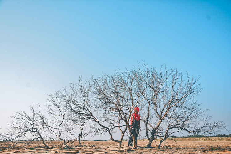 Woman standing by bare trees on land