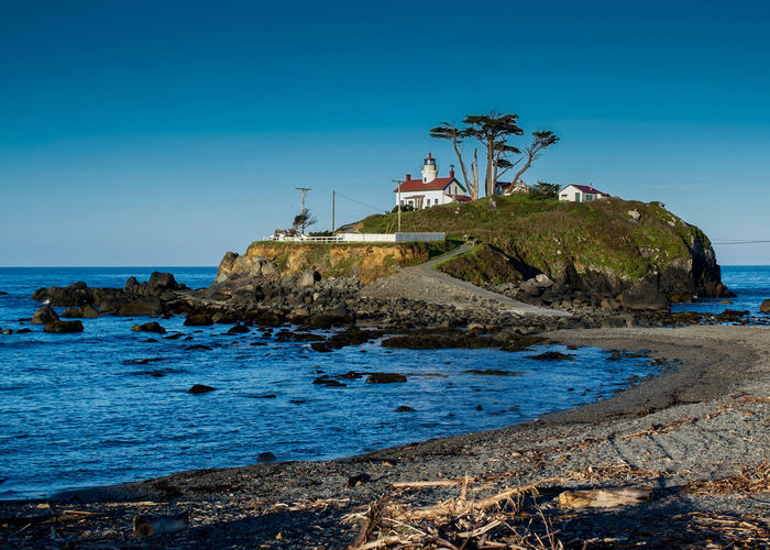 Battery Point Lighthouse in Crescent City, California, USA, on a cloudless day Water Sky Sea Built Structure Architecture Blue Land Nature Beach Building Exterior Day No People Clear Sky Scenics - Nature Beauty In Nature Outdoors Battery Point Lighthouse Crescent City, CA California USA Tourist Destination