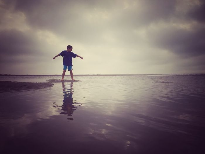 Full length of boy with arms outstretched standing at beach against sky