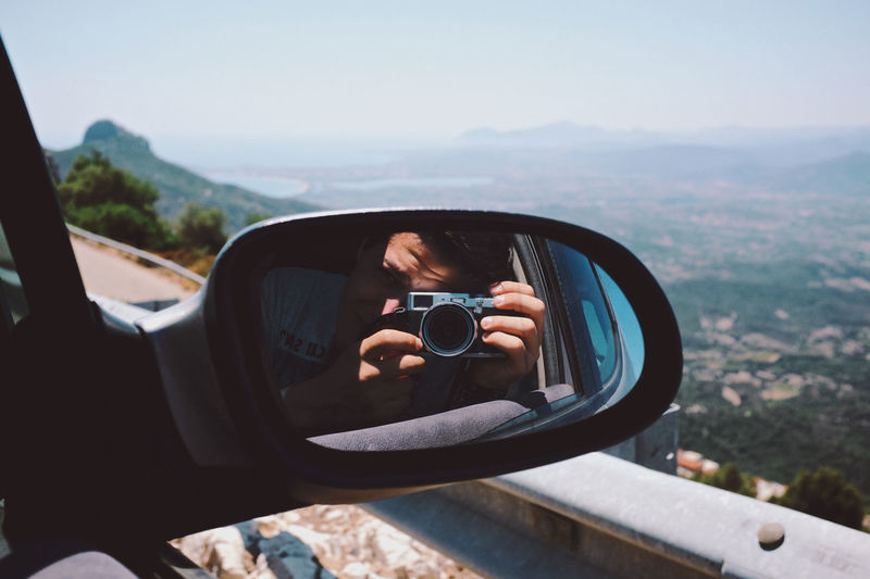 Man Taking Picture Of View With Camera From Car