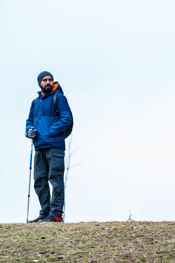 Full length of hiker standing on land against clear sky