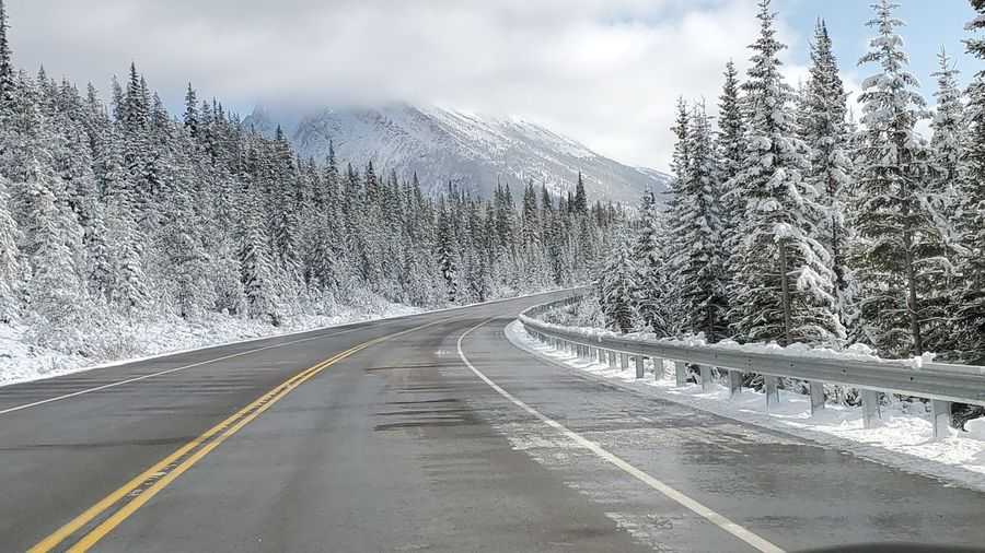 Road by snow covered mountain against sky