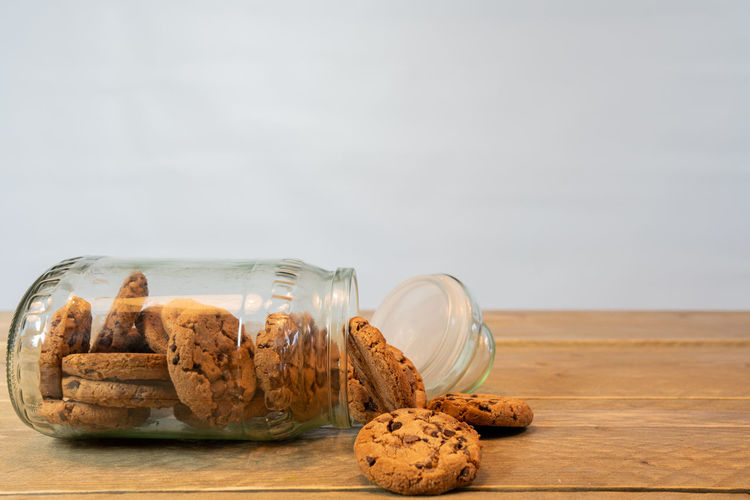 Glass jar with chocolate chip cookies on his side. Cookies out of the jar on the wooden table. White background Food And Drink Food Baked Still Life Cookie Table Sweet Food Indulgence Temptation Indoors  Freshness No People Wood - Material Close-up Chocolate Chip Cookie Ready-to-eat Unhealthy Eating Copy Space Chocolate Snack Glass Calories Tempting Temptation Tasty Backgrounds White Background Biscuit Cocoa Chocolate Yummy Brown Sweet Homemade Texture Wooden Table Side View Pastry Traditional Treat Childhood Eat Round