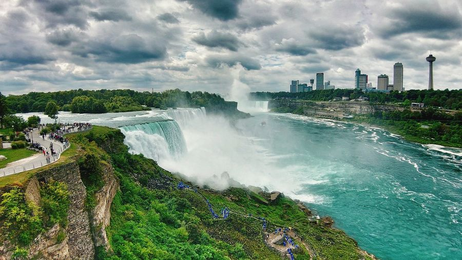Scenic view of waterfall against sky in city