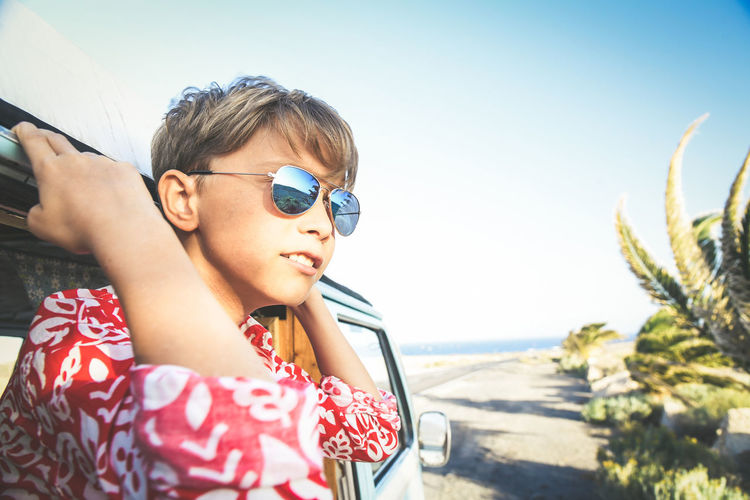Close-up of boy in car against sky