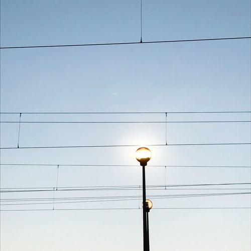 Low Angle View Of Power Lines And Illuminated Street Lights Against Clear Sky
