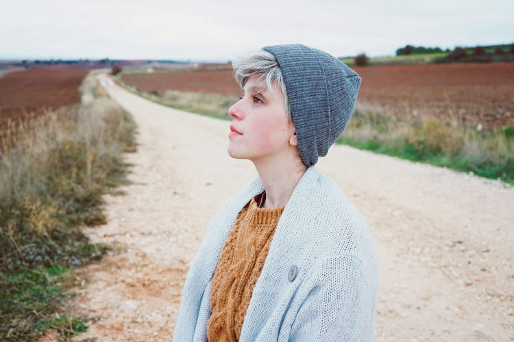 Close-Up Of Woman Wearing Knit Hat While Standing On Dirt Road